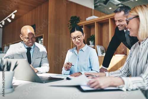 Laughing businesspeople going over paperwork together during an office meeeting Wallpaper Mural