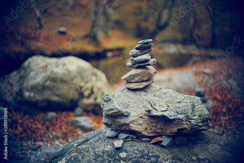 Acrylic Prints Zen Pyramid of stones by the river in the forest