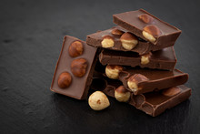 Milk Chocolate Pieces With Nuts On A Dark Background