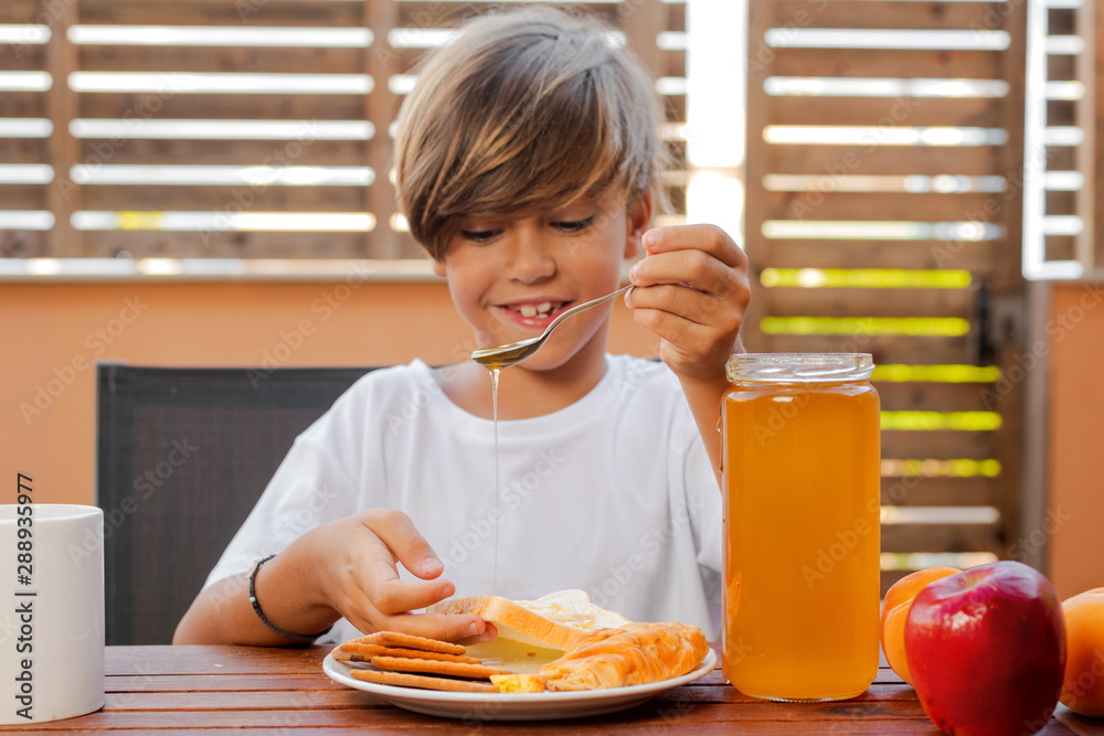 Obraz Child delivers honey on bread fototapeta, plakat
