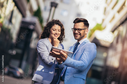 Handsome man and beautiful woman as business partners using digital tablet outdoor