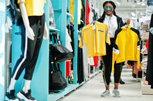 Afican American Women In Tracksuits And Sunglasses Shopping At Sportswear Mall Against Shelves. She Choose Yellow T-shirt. Sport Store Theme.