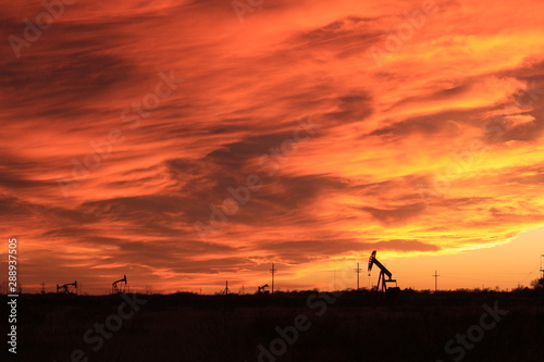 Poster Marron chocolat Wild sunset and oilfield pumpjacks.