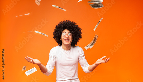 Fototapeta Excited black millennial guy enjoying rain of money obraz