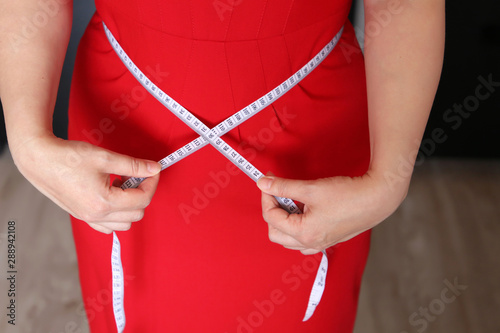 Fototapeta  Woman in red dress with measuring tape around the waist