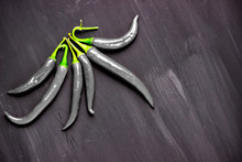 Studio Shot Of Group Of Black Chili Peppers Isolated On A Black Background.