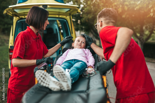 Fototapeta  Doctors with injured little girl in front of ambulance car.