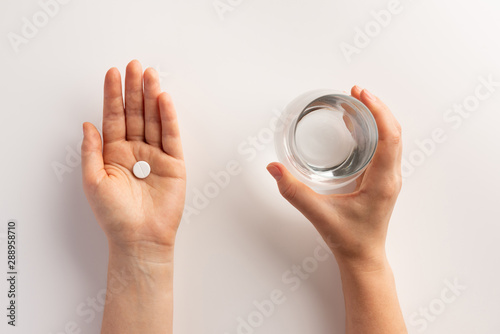 Healthcare and medical concept. Person holding pill in one hand and glass of water in the another hand. Flat lay.