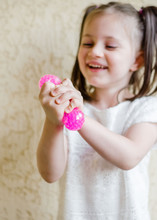 Child Girl Holding Stress Relief Grape Balls. Squeezing Balls, Mesh Squishy Balls In Kid's Hands
