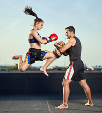Young Woman Kickboxer In Urban Environment, Training