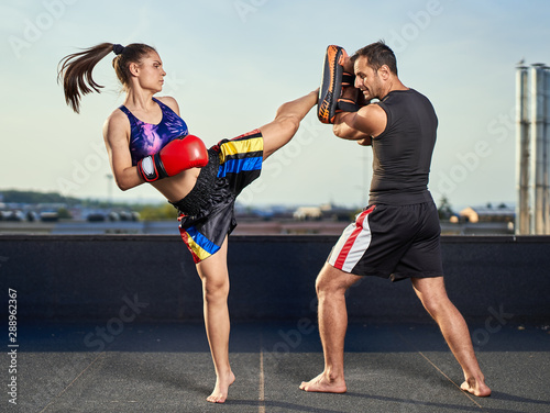 Photo  Young woman kickboxer in urban environment, training