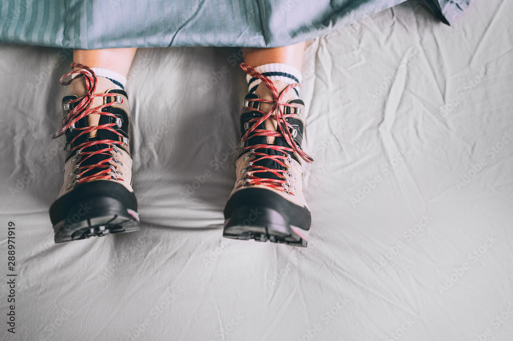 Fototapeta All time ready for trekking. Hiker sleeping in comfort trekking boots. Footwear on the bed sheet background concept image.