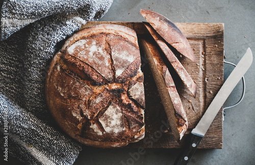 Fotografiet Flat-lay of freshly baked sourdough bread loaf and bread slices on rustic wooden