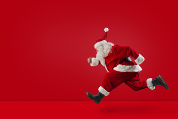 Santa Claus runs fast on red background