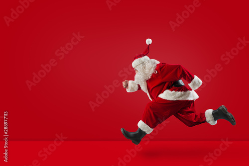 Fotomural  Santa Claus runs fast on red background