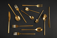 Flat Lay Composition With Gold Cutlery On Black Background