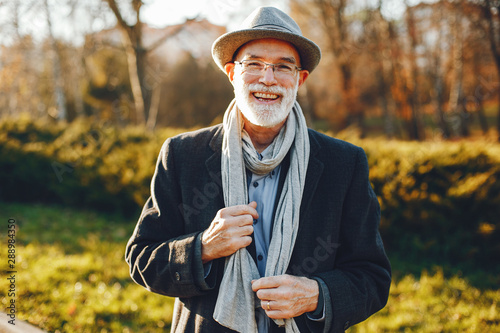 Obraz Handsome grandfather in a autumn park. Old man in a gray jacket and hat. - fototapety do salonu