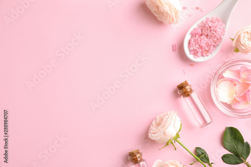 Flat lay composition with rose essential oil on pink background, space for text