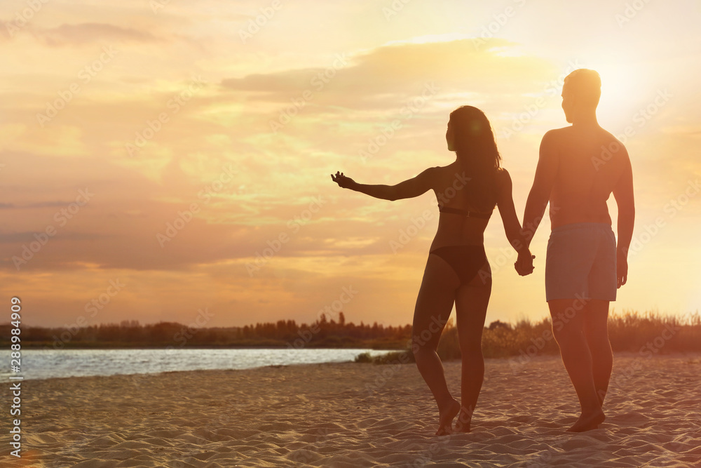 Fototapety, obrazy: Young woman in bikini spending time with her boyfriend on beach. Lovely couple