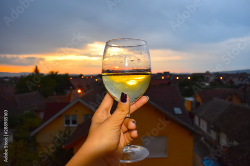 Foto op Canvas Oost Europa Female hand holding a glass of traditional Romanian chilled pelin white wine flavoured with a mixture of herbs. Sibiu, Romania, Eastern Europe