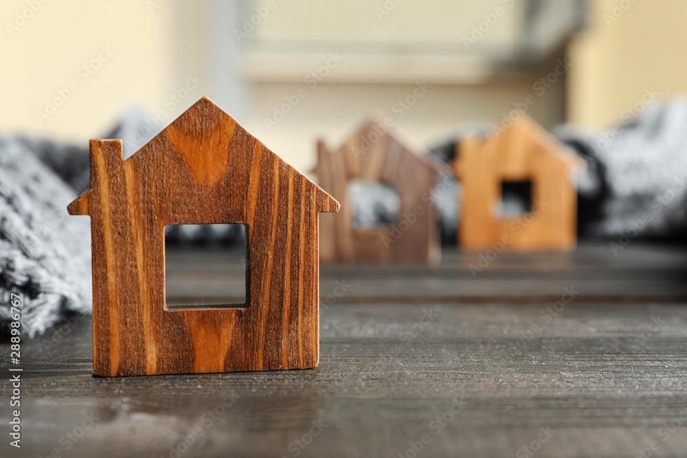 Fototapeta Wooden house model and scarf on grey table, space for text. Heating efficiency