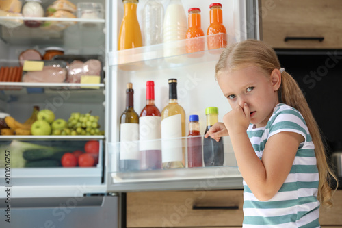 Photo Girl feeling bad smell from stale products in refrigerator at home