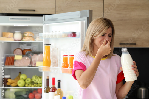 Woman taking bottle with old milk out of refrigerator in kitchen Canvas Print