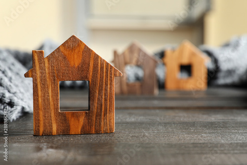 Wooden house model and scarf on grey table, space for text. Heating efficiency