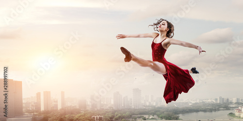 Young and beautiful female dancer in a red dress - 288997102