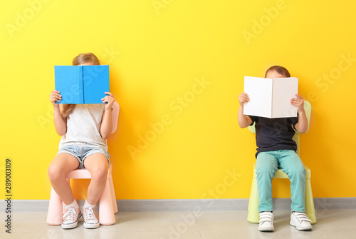 Obraz Little children with books sitting on chairs near color wall - fototapety do salonu