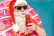Santa Claus With Inflatable Ring And Cocktail Near Swimming Pool At Resort