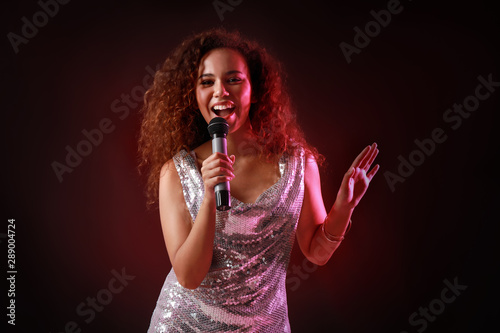 Beautiful African-American female singer with microphone on dark background