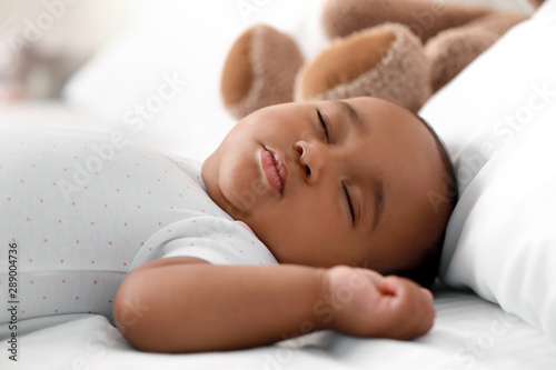 Obraz Cute African-American baby sleeping on bed - fototapety do salonu