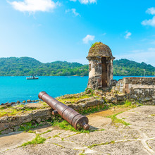 Square Photograph Of A Spanish Fort With Shooting Tower And Cannon Looking Over The Bay Of Portobelo Harbor By The Caribbean Sea To Protect The Spanish Customs Of Pirate Attacks, Panama.