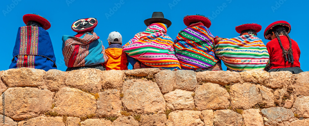 Fototapeta Panoramic photograph of Quechua indigenous women in traditional clothing with a boy sitting on an ancient Inca wall in Chinchero, Cusco Province, Peru.