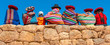 Leinwanddruck Bild - Panoramic photograph of Quechua indigenous women in traditional clothing with a boy sitting on an ancient Inca wall in Chinchero, Cusco Province, Peru.