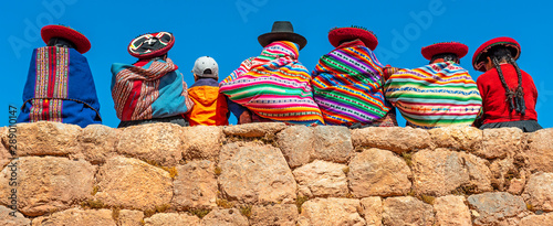 Fototapeta Panoramic photograph of Quechua indigenous women in traditional clothing with a boy sitting on an ancient Inca wall in Chinchero, Cusco Province, Peru. obraz