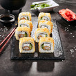 Leinwanddruck Bild Macro shot of hot crispy ebi tempura maki sushi rolls with cream cheese, king prawn, chuka kelp salad and nori. Deep fried uramaki roll set on natural black stone slate background closeup