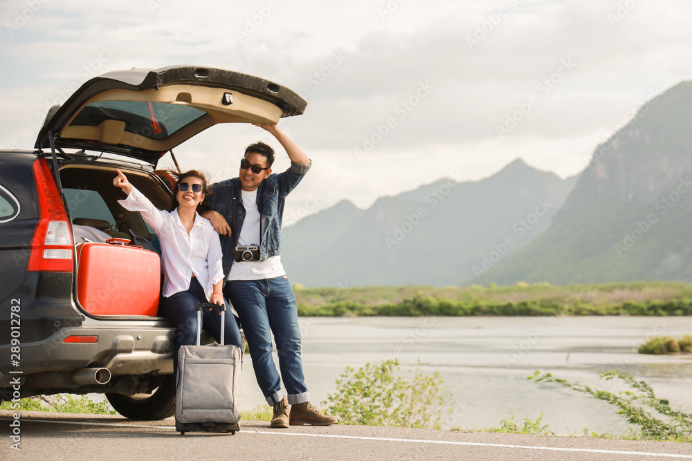 Fototapeta Asian couple Man with vintage camerra and woman sitting on back of car  travel to mountain and lake in holiday with car road trip