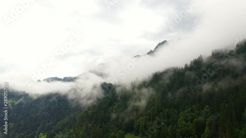 Aerial, tracking, drone shot, overlooking foggy forest, in the swiss alps, near the Lauterbrunnen village, on a cloudy, summer day, in Bernese Oberland, Switzerland - 289015752