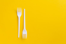 White Plastic Forks On Vibrant Yellow Background. Flatlay. Fast Food, Eco And No Plastic Concept. Copy Space.