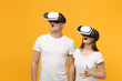 Young couple friends guy girl in white empty blank design t-shirts posing isolated on yellow orange background. People lifestyle concept. Mock up copy space. Watching in headset of vr virtual reality.