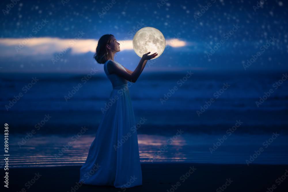 Fototapeta A young girl on a night beach holds the moon, with a starry sky. Art photography