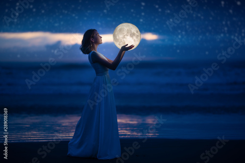 Fototapeta A young girl on a night beach holds the moon, with a starry sky. Art photography obraz