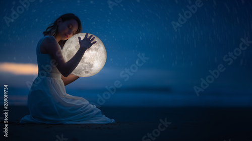 Tender image of a girl; female magic. Beautiful attractive girl on a night beach with sand and stars hugs the moon, art photo. On a dark background with space.