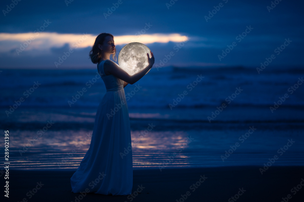 Fototapety, obrazy: Tender image of a girl. Female magic. Beautiful attractive girl in full growth on a night beach with sand hugs the moon, art photo. On a dark background with space. Riddle, astrology, zodiac. Banner.