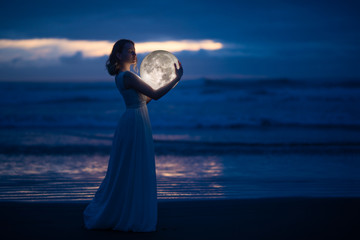 Tender image of a girl. Female magic. Beautiful attractive girl in full growth on a night beach with sand hugs the moon, art photo. On a dark background with space. Riddle, astrology, zodiac. Banner.