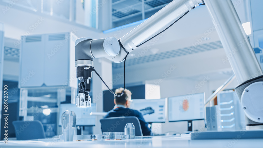 Fototapeta Modern Robot Arm Picks up, Lifts and Moves Metal Component as Programmed. In the Background Industrial Robotics Engineers Working on Software, Programming and Machine Learning in Engineering Facility