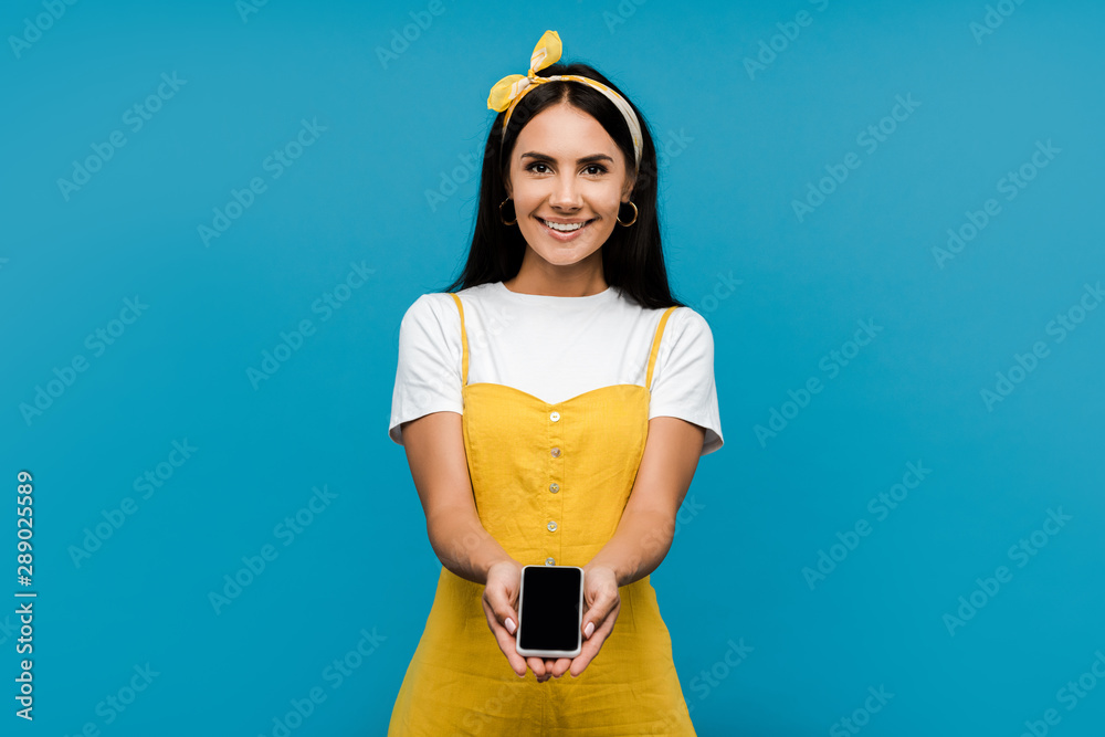 Fototapeta happy woman in yellow dress holding smartphone with blank screen isolated on blue