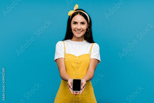 happy woman in yellow dress holding smartphone with blank screen isolated on blue